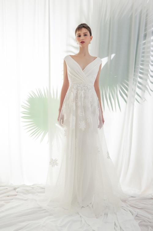 Xu hướng váy tối giản tiếp tục được áp dụng ở mẫu đầm này. Cổ áo được xếp lớp khéo léo tạo nên dấu ấn riêng cho mẫu váy cưới.