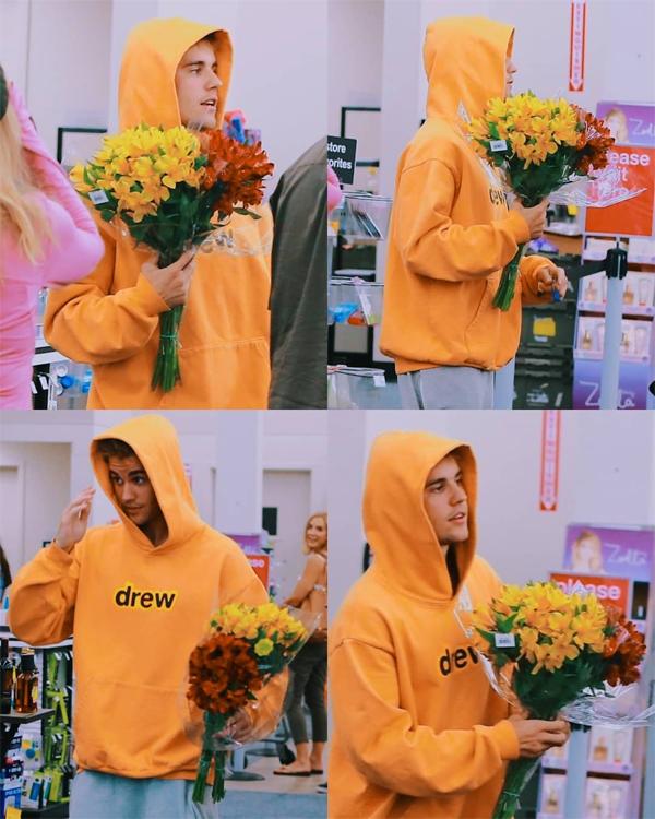 Justin Bieber hớn hở ôm bó hoa ra về.