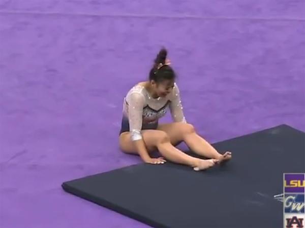 Samantha ngồi bệt xuống sàn đau đớn với hai chân trật khớp. Ảnh cắt từ video.