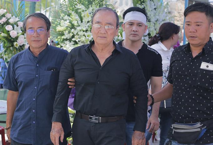 Bố Anh Vũ (giữa) mệt mỏi, tiều tuỵ sau 9 ngày chờ thi hài con trai được đưa về quê hương. Ông được hai người thân dìu đi trong lễ tang.