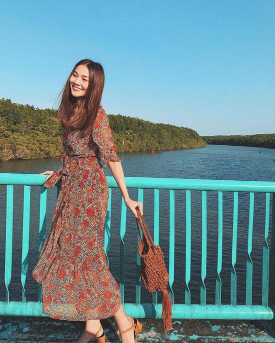 Đầm thắt eo mang hơi hướng cổ điển được siêu mẫu sử dụng cùng túi dây đan, sandal quai mảnh màn lại cảm giác tự do và thoải mái.