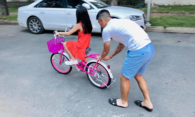 Công Vinh tập cho con gái đi xe đạp.