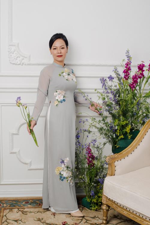 Tà áo dài ghi có họa tiết hoa cỏ được thêu nhấn nhá ở thân trên, eo và chân tà đóng vai trò thu hút ánh nhìn, giúp giấu đi vòng eo kém thon gọn của phụ nữ tuổi trung niên.