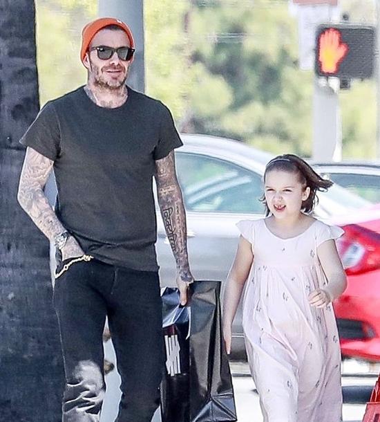 Becks mặc đồ đen nhưng nổi bật bởi chiếc mũ len màu cam, trong khi con gái cưng gây chú ý với