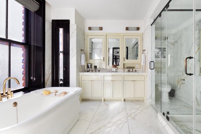Phòng tắm lớn được tích hợp ngay trong phòng ngủ với nội thất cao cấp mạ vàng, bồn tắmvòi hoa sen và gạch ốp tường được làm bằng đá cẩm thạch Calacatta Gold.