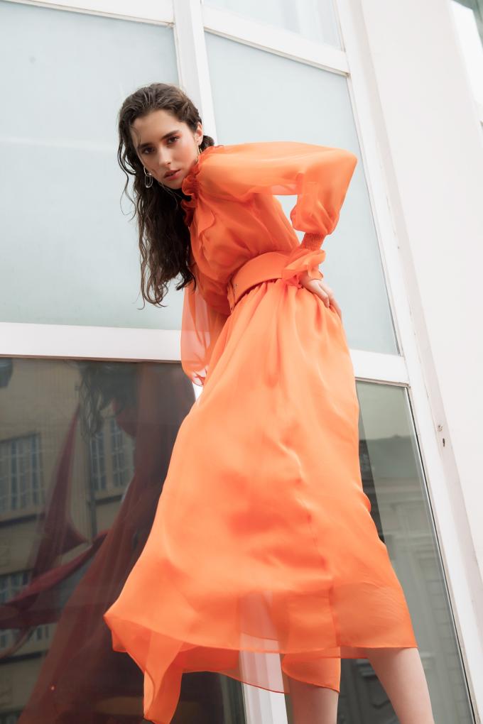 Đầm voan dài cóthiết kế xếp bèo cổ, dùng thắt lưng to bản làm điểm nhấn eo giúp người mặc nổi bật với sắc cam.