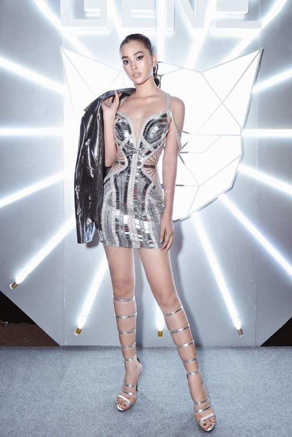 Váy hai dây cut-out sexy được hoa hậu phối hợp sandal chiến binh và áo jacket ánh bạc.