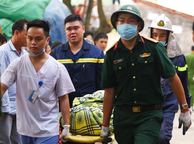 Lực lượng chức năng đưa người tử nạn trong đám cháy ở phường Trung Văn sáng 12/4 ra ngoà. Ảnh: Gia Chính.