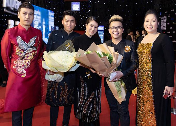 Diễn viên Ngọc Thuận (áo dài đỏ) và NSND Hồng Vân chúc mừng nhà thiết kế Minh Châu (đeo kính) ra mắt sưu tập thời trang mới.