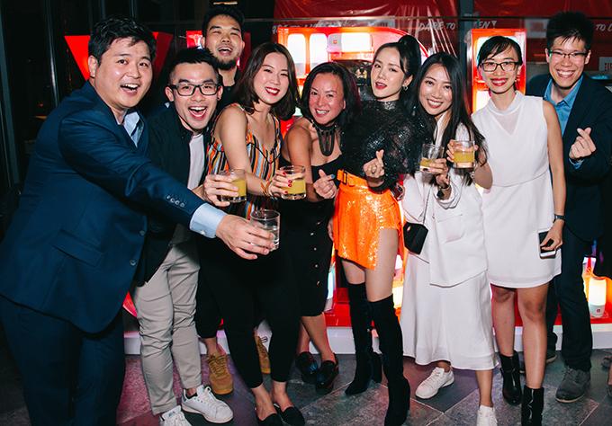 Nữ ca sĩ bắn tim chụp ảnh cùng một sốkhách mờitrong đêm tiệc.