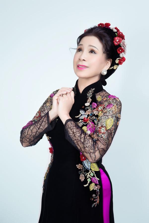 Áo dài gam màu trầm là sự lựa chọn thích hợp cho phụ nữ trung niên. Sắc đen kết hợp lớp ren tay đính pha lê và đường hoa dây dọc eo giúp tạo cảm giác vòng 2 thon gọn.