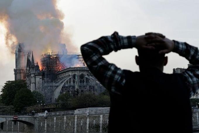 Người đàn ông ôm đầu bất lực khi chứng kiến công trình biểu tượng của Paris bốc cháy dữ dội. Ảnh: CNN.