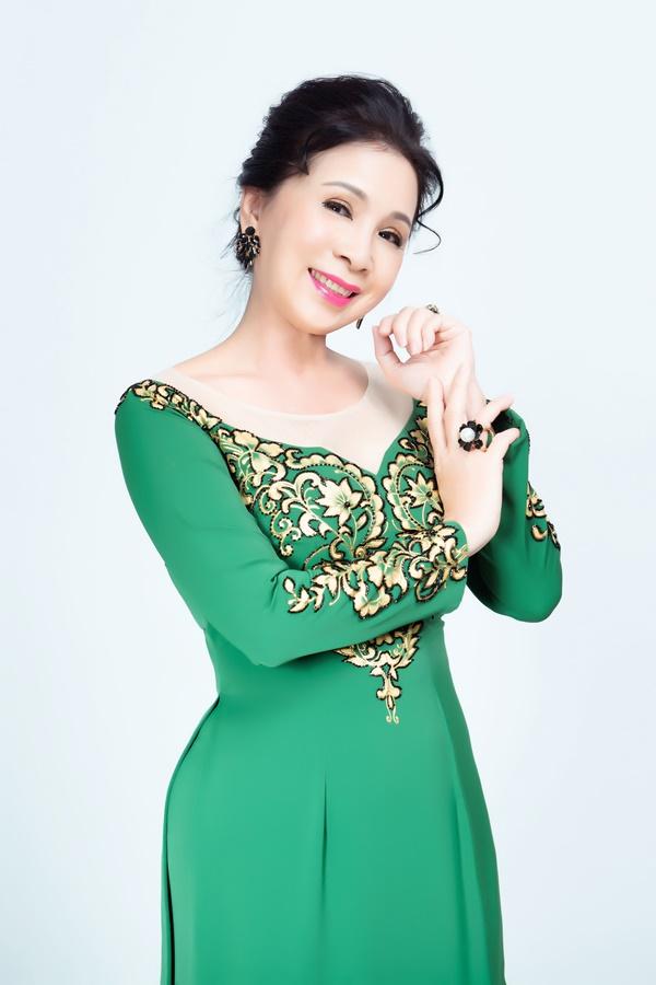 Thiết kế tay áo dài truyền thống giúp che đi nhược điểm bắp tay to của  phụ nữ ngoài 40 tuổi. Chi tiết hoa lá cách điệu trên nền xanh tạo ấn tượng.