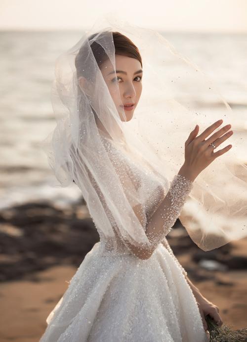 Trong bộ ảnh, Lê Hà diện các váy cưới để chụp hình đến từ NTK Linh Ng. Bộ đầm mng phom dáng xòe phồng mà cô diệnlấy ý tưởng từ giọt sương mi, được đính kết 5.000 viên ph lê Swrovski tạo vẻ lộng lẫy, bắt mắt.