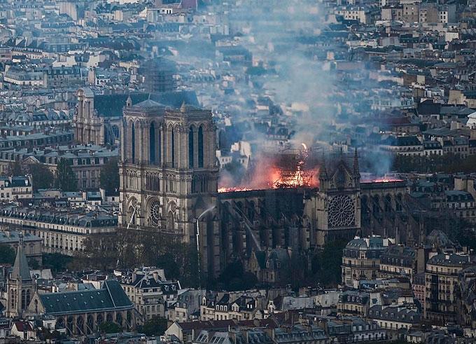 Ngọn lửa bốc lên từ phần mái của Nhà thờ Đức Bà Paris chiều tối 15/4. Ảnh: AFP.
