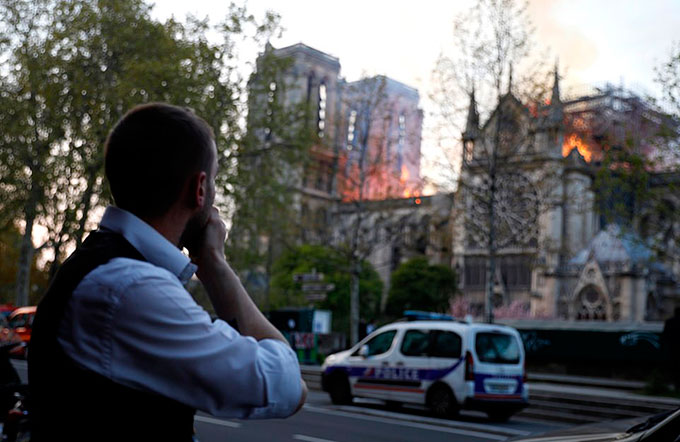 Một người dân Pháp bịt miệng xót xa khi chứng kiến cảnh Nhà thờ Đức Bà Paris bốc cháy tối 15/4. Ảnh: EPA.