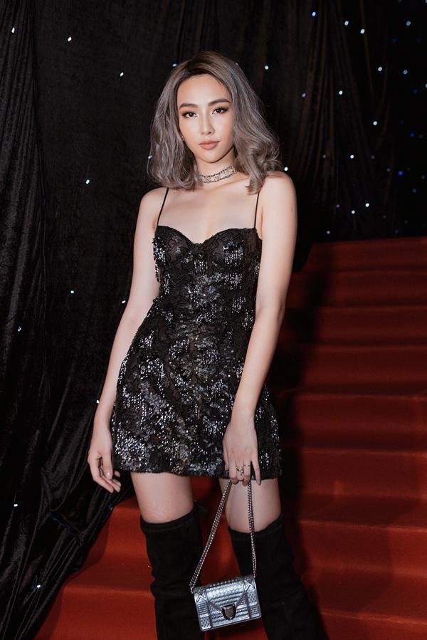 Thùy Tiên thể hiện sự cá tính với cách phối váy hai dây ánh kim, bốt cao cổ và túi Dior màu ánh bạc hợp xu hướng.