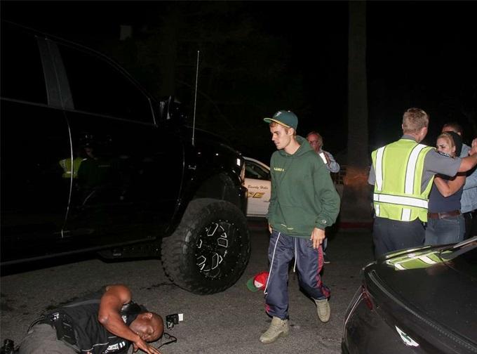 Justin Bieber (áo xanh) ở lại hiện trường vụ tai nạn 2 năm trước.