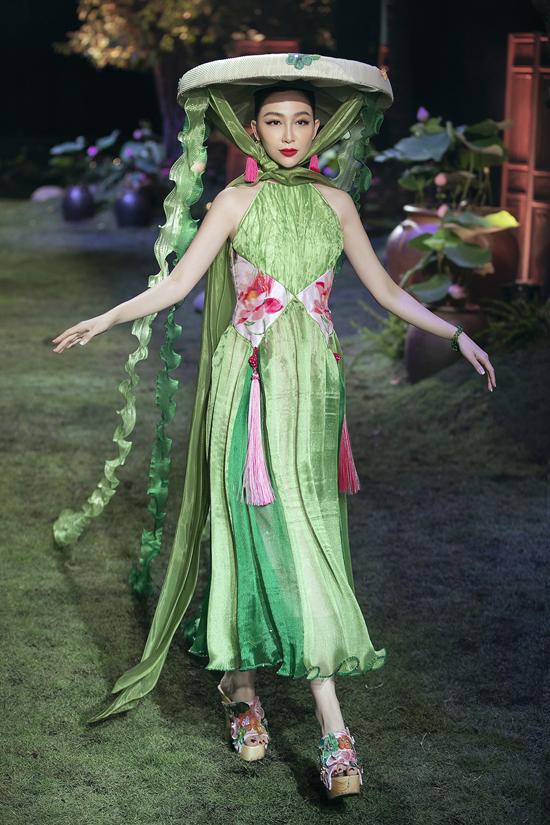 Nữ diễn viên múa đội nón quai thao đi quốc trang trí thủ công trình diễn áo yếm trên chất liệu lụa mềm óng ả. Đây cũng là chất liệu chủ đạo trong bộ sưu tập dành cho mùa xuân hè của Thủy Nguyễn.