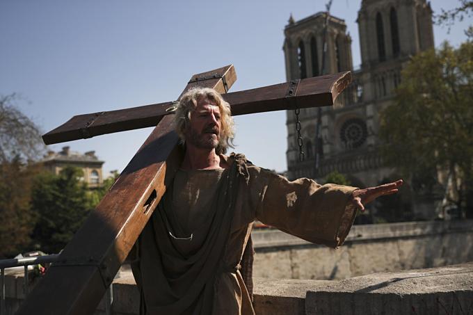 Người biểu tình cải trang thành Chúa Jesus, vác thậpgía gầnnhà thờ mới cháy để đòi quyền lợicho dânnghèo. Ảnh: AP.