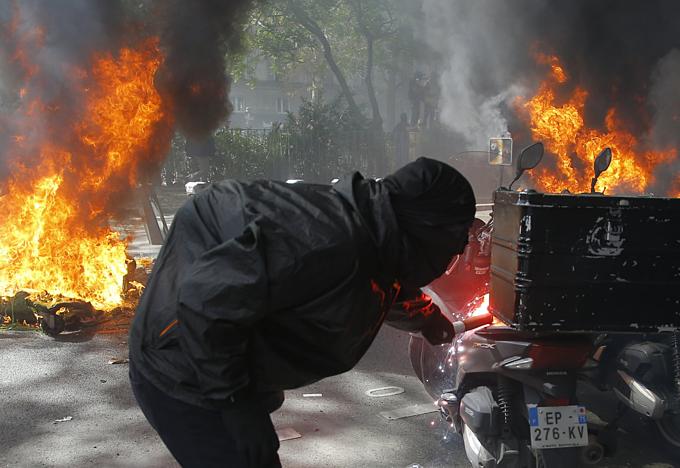 Một người biểu tình quá khích châm lửa đốt xe máy tại Paris ngày20/4. Ảnh: AP.