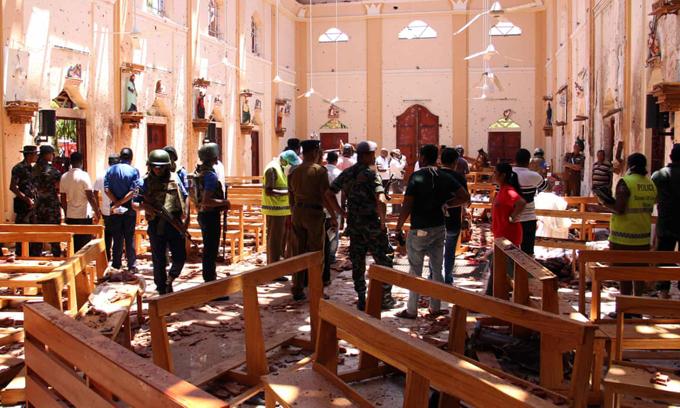 Sri Lankan security personnel walk through debris following the explosion in St Sebastian's Church in Negombo. Photograph: STR/AFP/