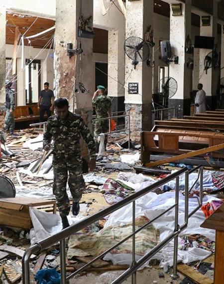 Lính Sri Lanka đi qua những thi thể được phủ chăn trên nền nhà ở đền Thánh Anthony. Ảnh: AFP.