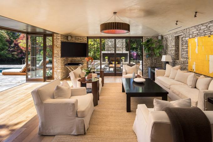 Không gian phòng khách mở, hướng mặt ra hồ bơi và lấy ánh sáng tự nhiên từ bên ngoài.