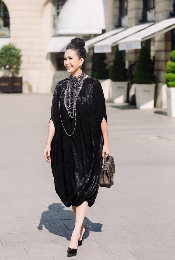 Bà mẹ hai con giấu đường cong trong dáng váy rộng với phần tay xẻ độc đáo. Họa tiết in trên vải tạo hiệu ứng bắt sáng, giúp người mặc dễ dàng thu hút chú ý. Ngoài ra, chiếc túi da kỳ nhông mới nhất của Celine giá 180 triệu đồng cũng tăng vẻ ấn tượng cho tổng thể.