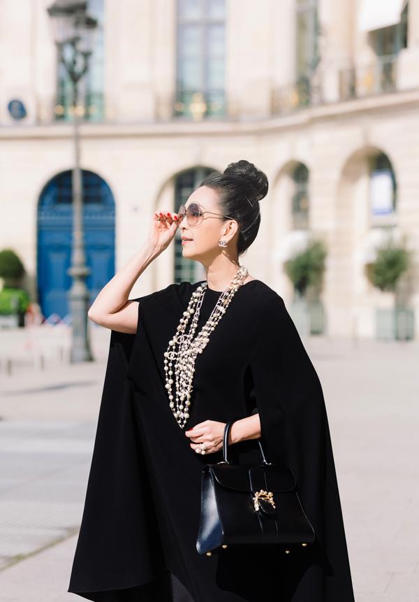 Với đầm cape sang trọng, Diễm My tạo điểm nhấn bằng chuỗi vòng cổ ngọc trai Chanel, nhẫn to bản và kính râm Celine, xách túi gam màu đồng điệu của Delvaux - một thương hiệu đồ da cao cấp của Bỉ có lịch sử gần 200 năm.