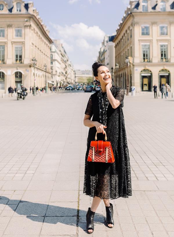 Mẫu túi Goyard đỏ tươi, giá khoảng 5.000 Euro (hơn 130 triệu đồng) trở thành điểm nhấn nổi bật trên nền váy ren nữ tính. Bên cạnh đó, đôi bốt da hở mũi Chanel cũng bổ sung nét trẻ trung, thời thượng cho diện mạo.