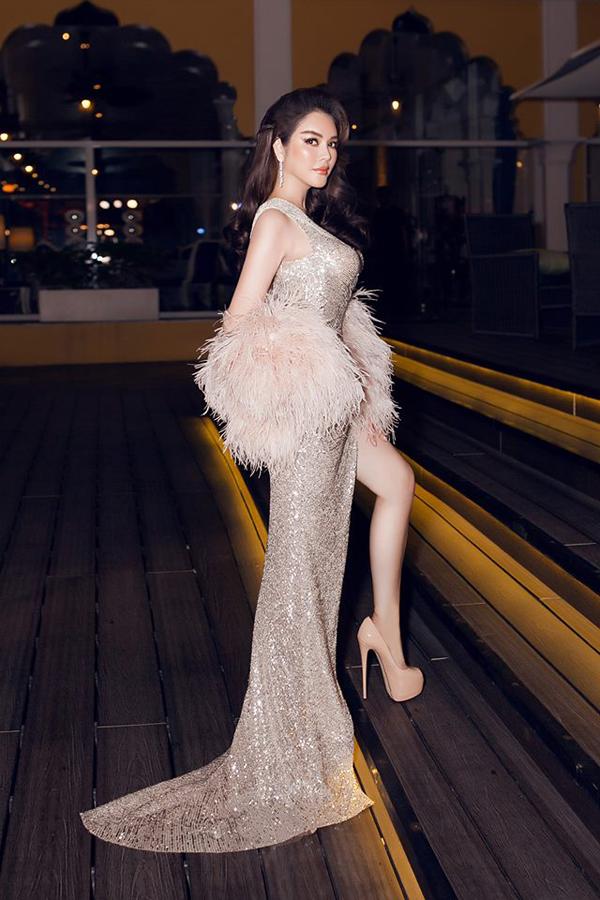 Lý Nhã Kỳ khoe nét quyến rũ và sexy với mẫu đầm lấp lánh của Đỗ Long. Đi cùng trang phục cắt may trên chất liệu bắt sáng là khăn choàng nhẹ bằng lông vũ mềm mại.