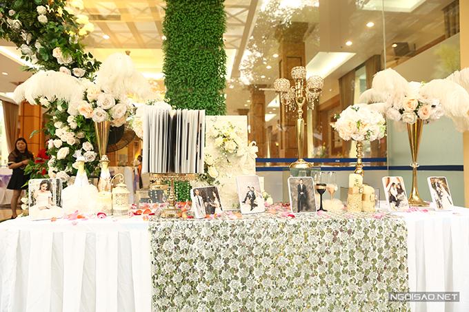 Ảnh cưới của cặp vợ chồng được trưng bày ở bàn gallery. Cỏ lau, hoa hồng tươi đóng vai trò giúp không gian thêm lãng mạn.