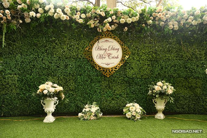 Khu vực photobooth tại tiệc cưới được trang trí đơn giản với hoa hồng tươi theo sở thích của uyên ương và lá cây xanh mát mắt.