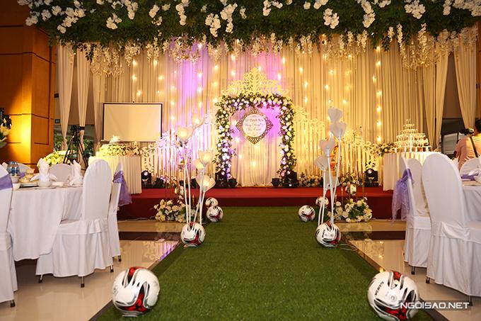Khu vực sân khấu tiệc mang phong cách hoàng gia với cổng hoa hình chữ nhật. Phía trên trần nhà là dàn hoa hồng trắng mang đến vẻ lãng mạn.