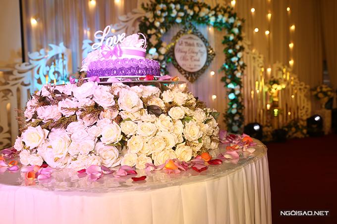 Bánh cưới của uyên ương có hai tầng và được tô điểm với hoa hồng trắng.