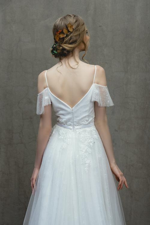 Thân váy được điểm họa tiết dây leo chạy dọc tạo điểm nhấn cho thiết kế. Bờ vai thon và tấm lưng trần gợi cảm của cô dâu là yếu tố thu hút ánh nhìn ở mặt sau lưng váy.