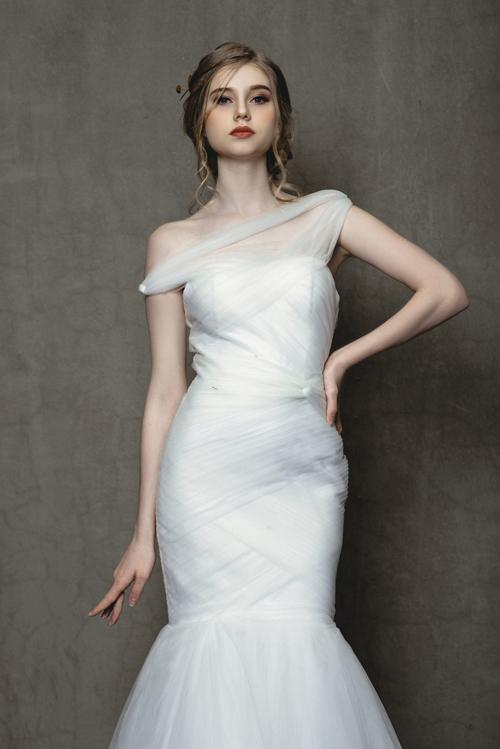 Mẫu váy đuôi cá mang tên Ann có đường xếp ly tinh tế giúp tôn đường cong gợi cảm của cô dâu mùa hạ.Cầu vai bất đối xứng tạo điểm nhấn giúp khoe nước da sáng của cô dâu mới.