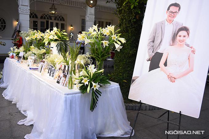 Vì đám cưới diễn ra đúng mùa hoa loa kèn nở rộ nên uyên ương đã chọn loài hoa này để trang trí tiệc ở nhà hàng. Ngoài hoa loa kèn, bàn gallery còn được tô điểm bởi ảnh cưới của hai vợ chồng.