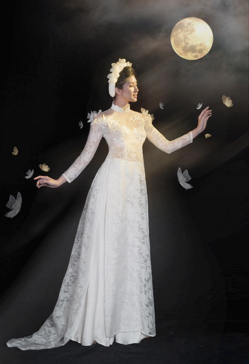 Mẫu áo dài trắng cũng là trang phục được nhiều nàng dâu lựa chọn cho dịp đại hỷ. Cảm hứng làm nên mẫu áo này là hình ảnh của chị Hằng trên cung trăng. Sự thanh thoát, dịu dàng được truyền tải ở trang phục thông qua chất liệu voan hoa cùng lớp lụa tằm bên trong. Cườm, kim sa được đính trên những cánh bướm 3D để tạo sự nổi bật, bắt sáng. Mẫu áo có giá bán 9,5 triệu đồng, giá thuê 3,5 triệu đồng. Trang phục: Áo dài La Sen Vũ