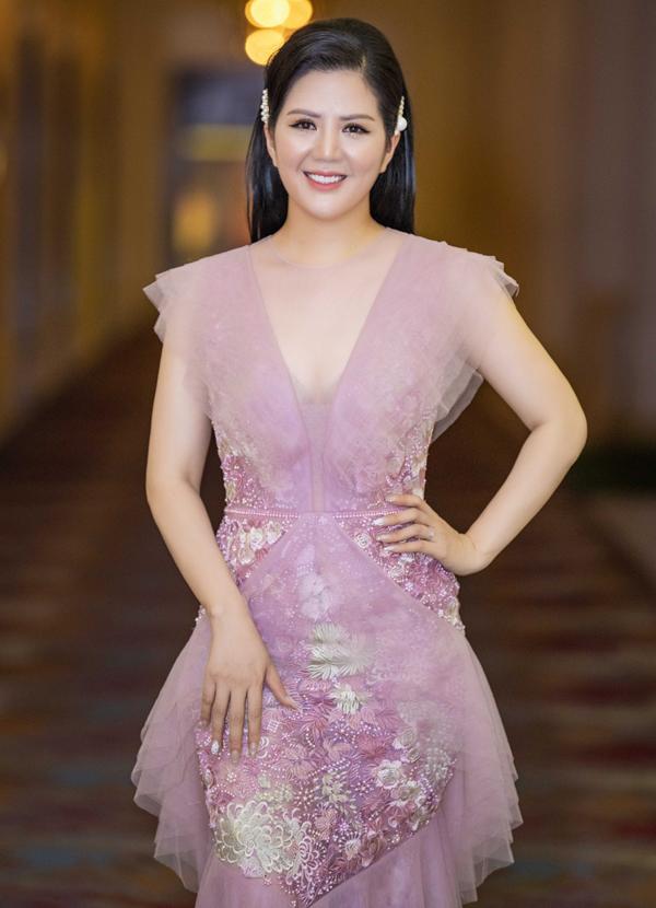 Ca sĩ lộng lẫy với váy dạ hội màu tím nhạt.