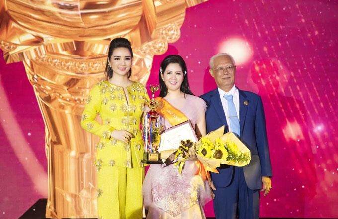 Ca sĩ Đinh Hiền Anh (giữa) lên sân khấu nhận giải thưởng Bông hồng Quyền lực - Nhân vật của năm 2019.