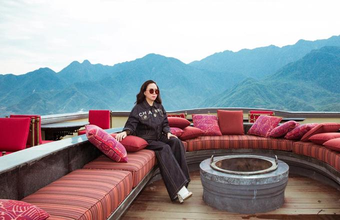 Nữ doanh nhân thích thú ngồi thư giãn, ngắm cảnh Sapa mù sương từ trên sân thượng của khách sạn.