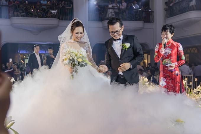 Sợ vợ trẻ di chuyển khó khăn trong bộ váy cưới bồng bềnh, sân khấu lại phủ đầy khói nên Trung Hiếu ân cần dìu vợ bước đi.