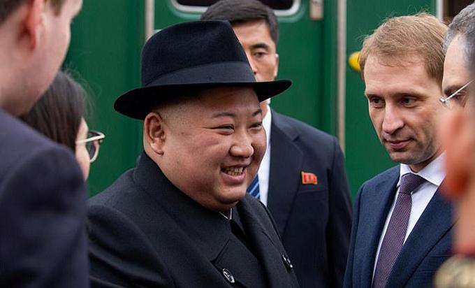 Kim Jong-un tươi cười bắt tay các quan chức Nga đang chờ đón mình ở nhà ga Khasan hôm 24/4. Ảnh: Reuters.
