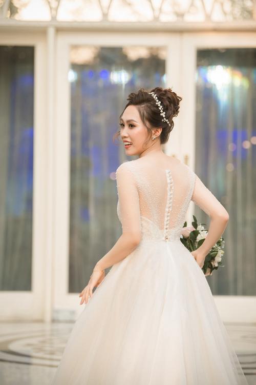 Không chỉ chú trọng ở mặt trước mà mặt lưng váy cũng là điểm thu hút ánh nhìn, giúp cô dâu tỏa sáng trong mọi khung hình. Hàng cúc ngọc trai ở lưng váy góp phần điểm tô nét nữ tính cho tấm lưng thon ẩn hiện dưới làn voan mỏng.