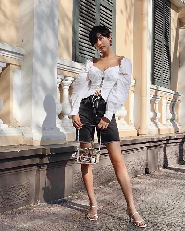 Khánh Linh The Face cá tính với mốt áo blouse tay bồng đi kèm quần short ảnh hưởng phong cách jeans biker. Túi nhựa trong, sandal quai mảnh là các món đồ khiến set đồ mùa hè trông bắt mắt hơn.