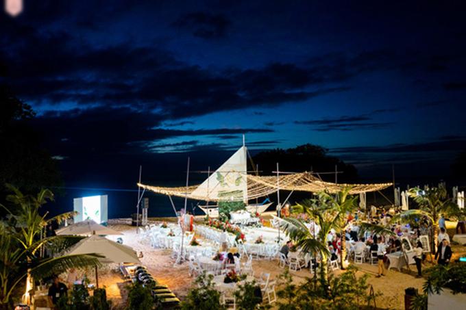 Không gian tiệc cưới được dựng trên bãi biển. Uyên ương chọn bàn tròn, ghế xếp - những vật dụng dễ di chuyển, xếp gọn cho phù hợp với bối cảnh cưới.