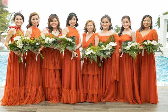 Dàn phù dâu diện váy chữ A mang sắc cam rực rỡ. Tuy cùng là váy chữ A nhưng mỗi chiếc váy đều được biến tấu ở cổ hoặc có thân dưới được thiết kế tầng bậc, tạo nên dấu ấn riêng. Mỗi cô gái cầm theo một bó hoa dáng dài gồm hồng môn trắng và lá cây cỏ vùng nhiệt đới.