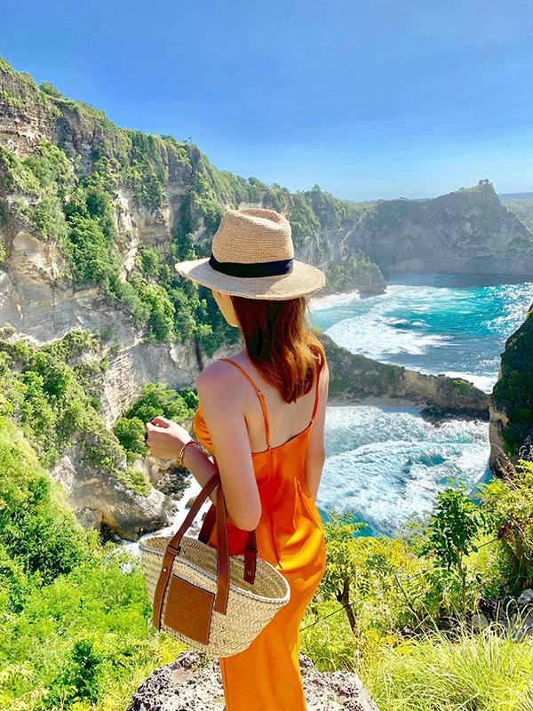 Váy lụa hai dây cùng các phụ kiện hot trend mùa hè như mũ nan, túi cói giúp Kỳ Duyên sành điệu và phong cách hơn khi đi du lịch.